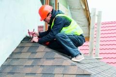 Roofer builder worker dismantling roof shingles